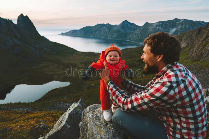 Father hiking with infant baby travel family healthy lifestyle adventure vacations trip in mountains stock photography