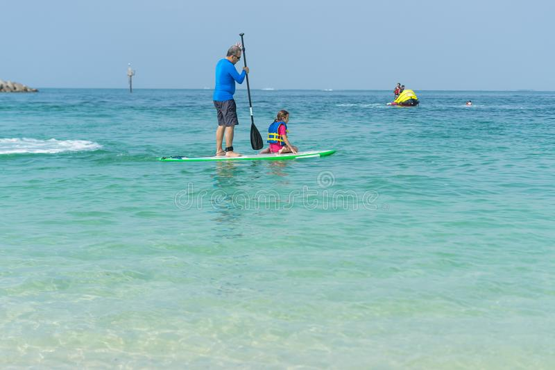 Father and his adorable little daughter sitting on stand up board having fun during summer beach vacation. Sea royalty free stock photography