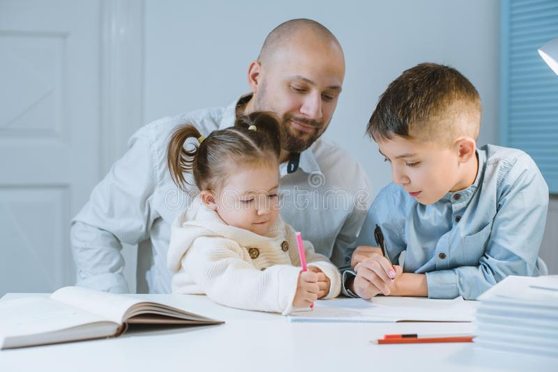 Father with his children have fun sitting at a table. stock image