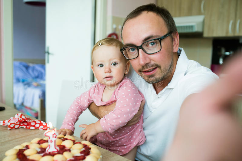 Father with his daughter and birthday cake, taking selfie royalty free stock images