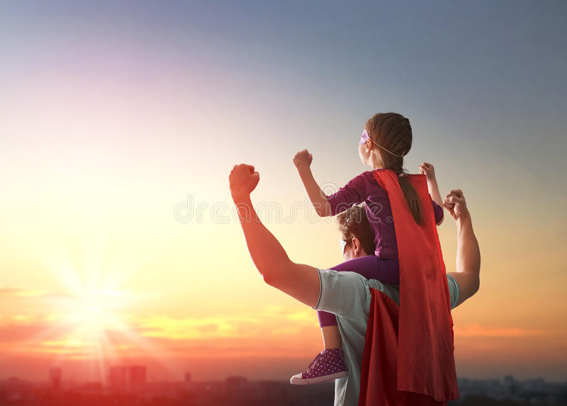 Father and his daughter. Happy loving family. Father and his daughter child girl playing outdoors. Daddy and his child girl in an Superhero's costumes. Concept