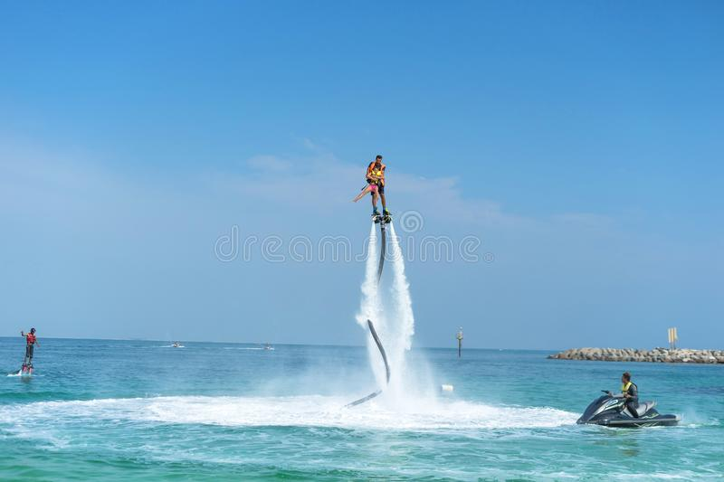 Father and his daughter posing at new flyboard at tropical beach. Positive human emotions, feelings, joy. Funny cute child making stock photography