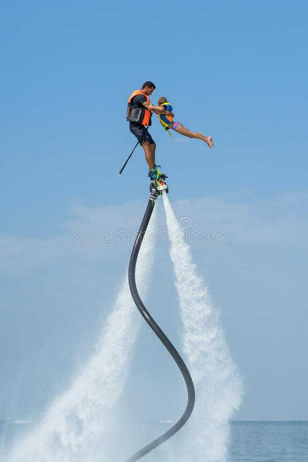Father and his daughter posing at new flyboard at Caribbean tropical beach. Positive human emotions, feelings, joy. Funny cute chi. Ld making vacations and royalty free stock photography