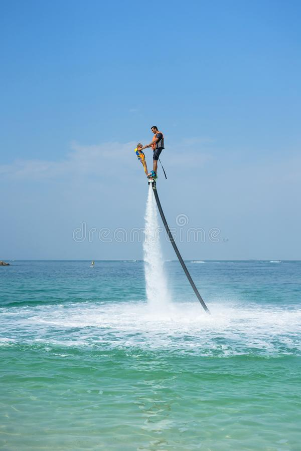 Father and his daughter posing at new flyboard at Caribbean tropical beach. Positive human emotions, feelings, joy. Funny cute chi stock image