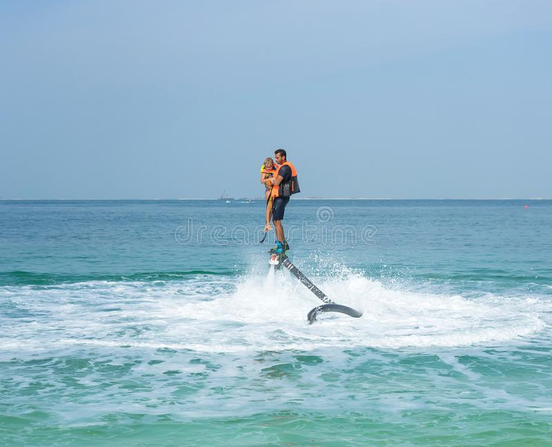 Father and his daughter posing at new flyboard at Caribbean tropical beach. Positive human emotions, feelings, joy. Funny cute chi royalty free stock photos