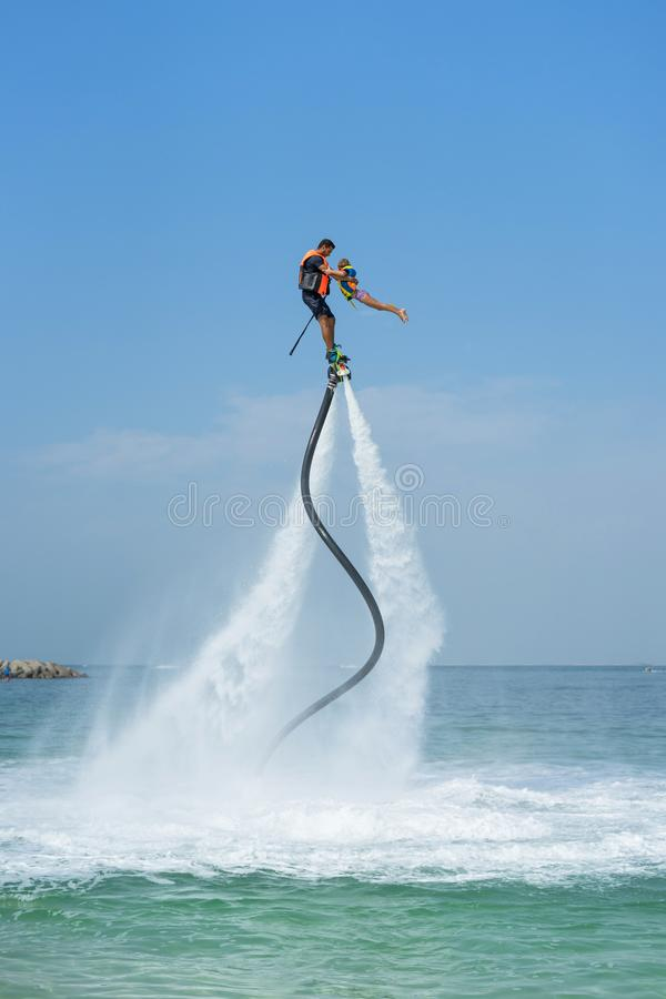 Father and his daughter posing at new flyboard at Caribbean tropical beach. Positive human emotions, feelings, joy. Funny cute chi. Ld making vacations and stock photos