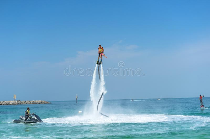 Father and his daughter posing at new flyboard at Caribbean tropical beach. Positive human emotions, feelings, joy. Funny cute chi royalty free stock photo
