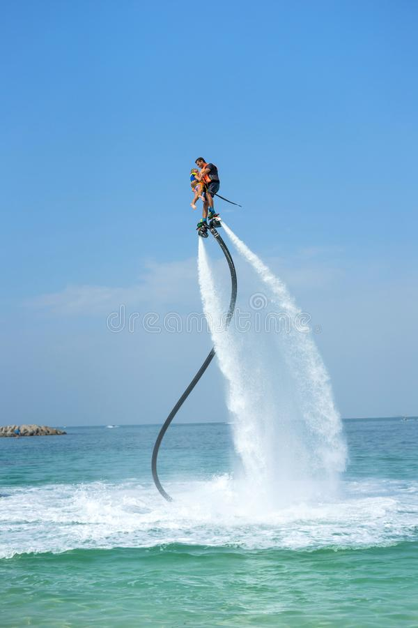 Father and his daughter posing at new flyboard at Caribbean tropical beach. Positive human emotions, feelings, joy. Funny cute chi royalty free stock photography