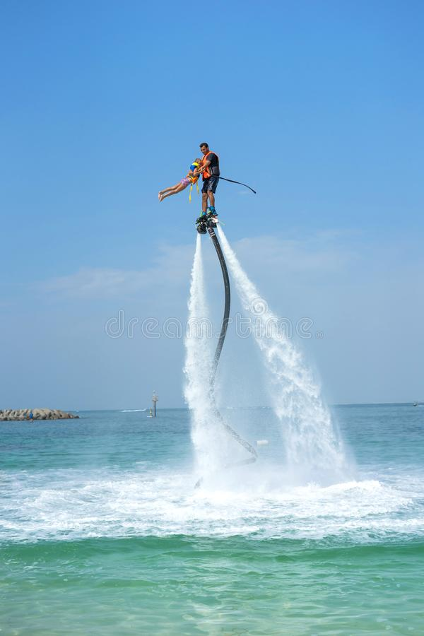 Father and his daughter posing at new flyboard at Caribbean tropical beach. Positive human emotions, feelings, joy. Funny cute chi. Ld making vacations and stock photo
