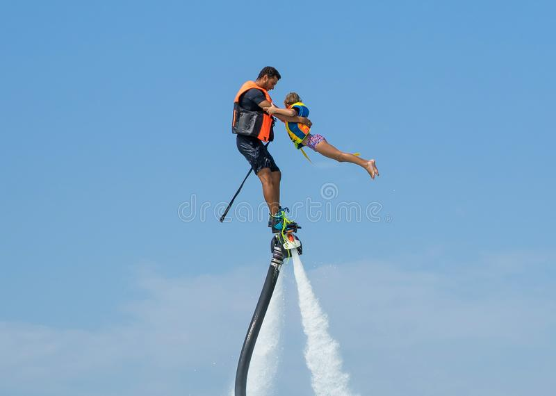 Father and his daughter posing at new flyboard at Caribbean tropical beach. Positive human emotions, feelings, joy. Funny cute chi stock photo
