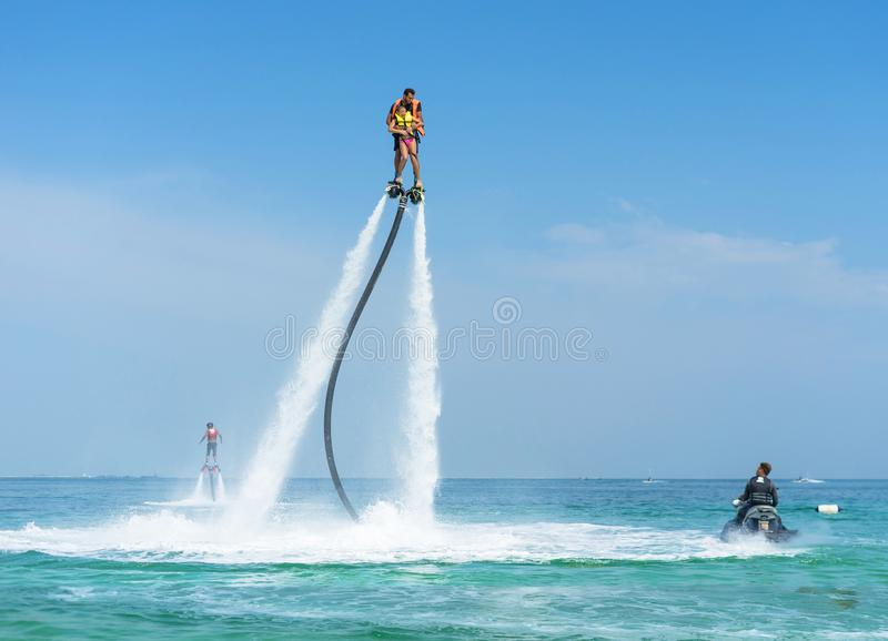 Father and his daughter posing at new flyboard at tropical beach. Positive human emotions, feelings, joy. Funny cute child making royalty free stock images