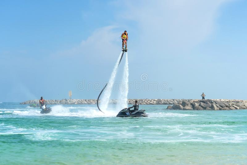 Father and his daughter posing at new flyboard at tropical beach. Positive human emotions, feelings, joy. Funny cute child making stock image