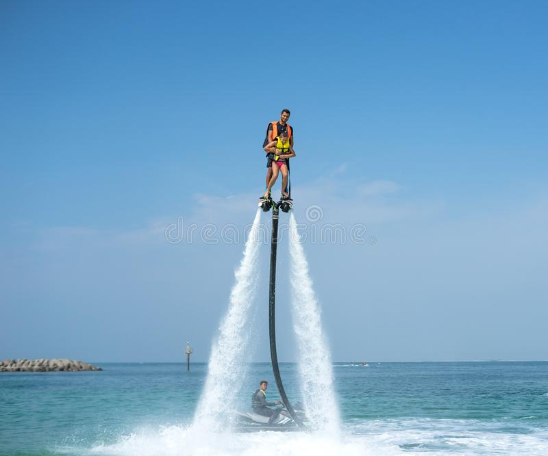Father and his daughter posing at new flyboard at tropical beach. Positive human emotions, feelings, joy. Funny cute child making royalty free stock photo