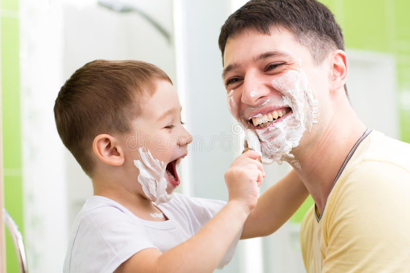 Father and his kid son playing in bathroom. Child boy putting shaving cream on dad face royalty free stock photo