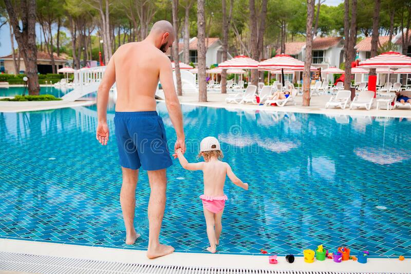 Father and his little baby daughter in a pool stock images