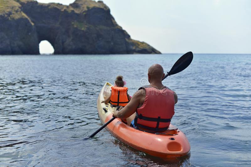 A father and his little daughter are sailing on the sea in a kayak to a grotto royalty free stock photos