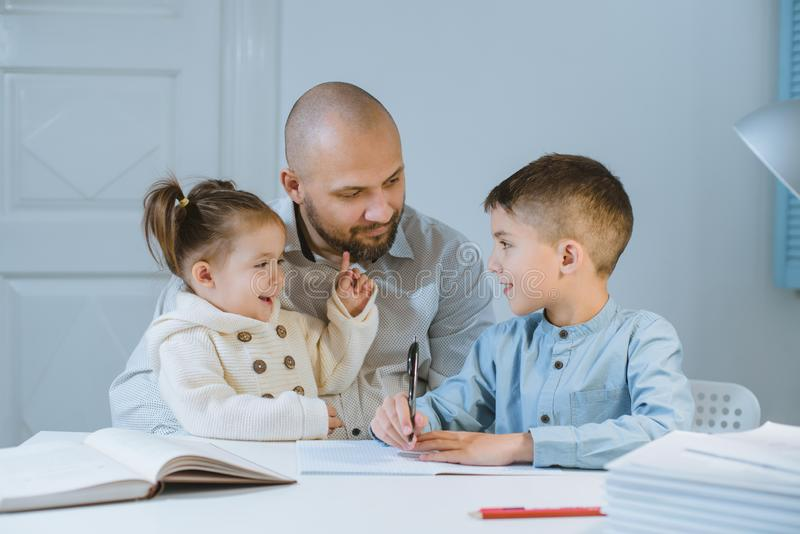 Father with his children have fun sitting at a table. royalty free stock images