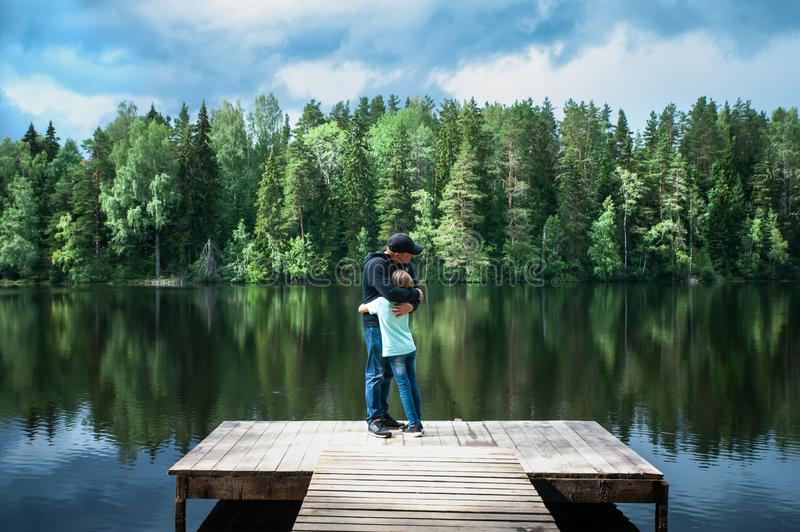 Father and his little daughter stand embracing on the pier of a beautiful lake. Father and daughter relationship concept royalty free stock photography