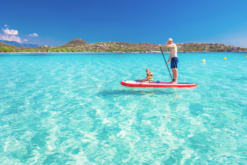 Father with his little happy son having fun on stand up paddle board stock images