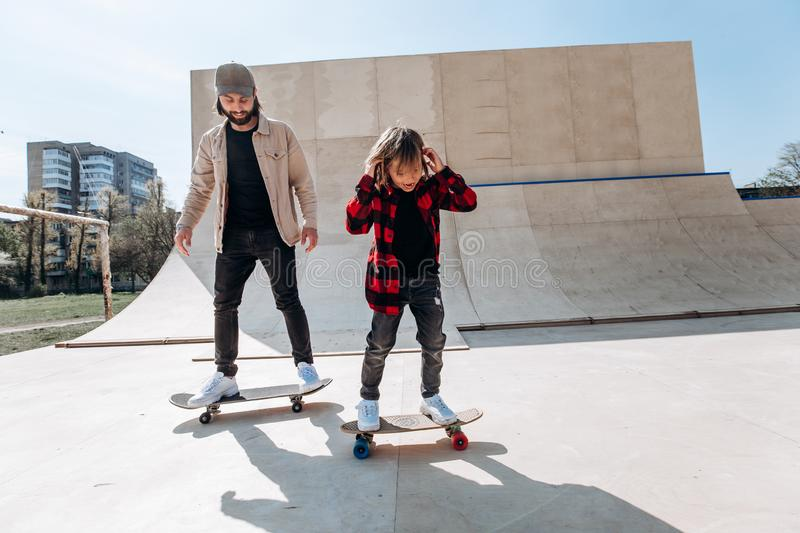 Father and his little son dressed in the casual clothes ride skateboards in a skate park with slides outside at the stock images