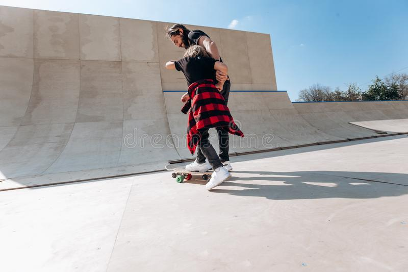 Father and his little son dressed in the casual clothes ride skateboards in a skate park with slides at the sunny day stock images