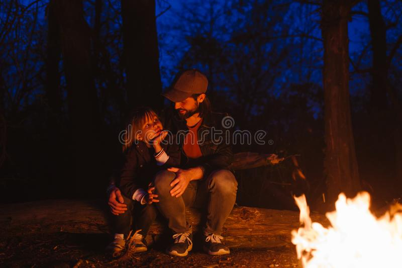 Father and his little son sitting together on the logs in front of a fire in a hike in the forest at the night. stock photos