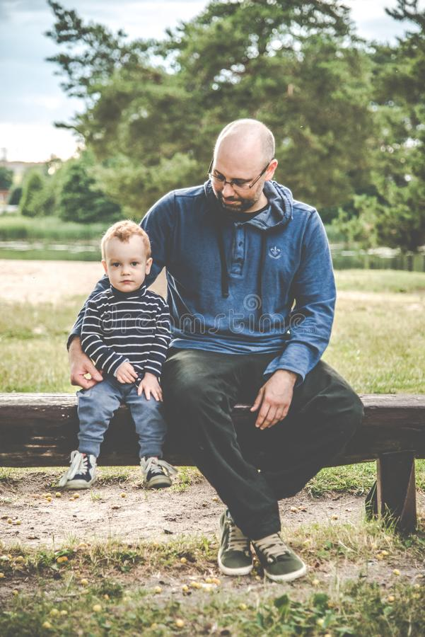 Father and son sitting on a bench stock images
