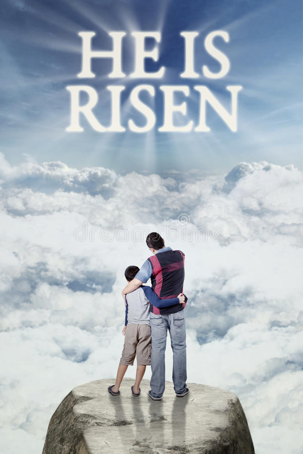 Father with his son looking at text he is risen. Image of young father standing on the cliff with his son and looking at text he is risen on the sky royalty free stock photography