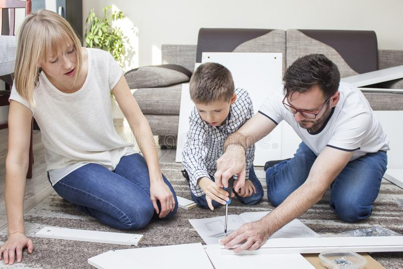 Father, with his son and mum, twist furniture. The boy is holding a screwdriver and the father helps to screw the screw. Mom l royalty free stock image