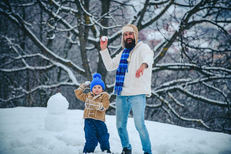 Father and his son playing outdoors. Cute little child boy and happy father on snowy field outdoor. Winter family in stock image