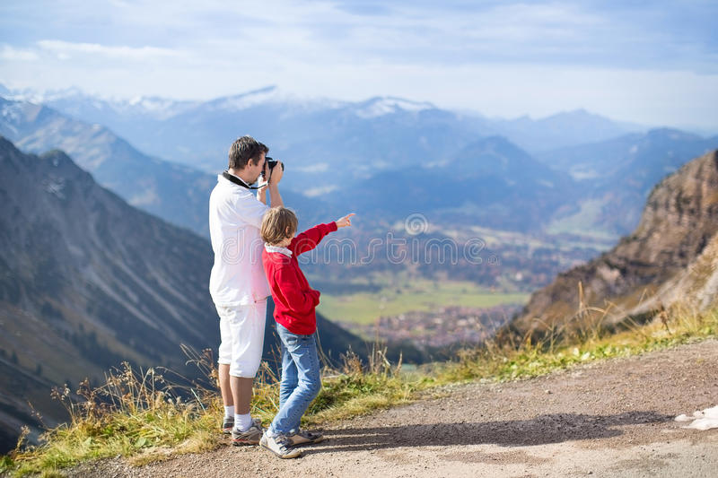 Father and his son taking pictures of mountais stock photography