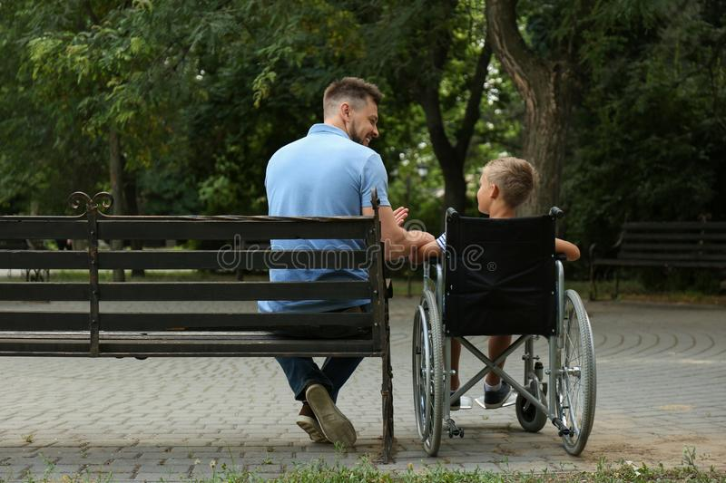 Father with his son in wheelchair at royalty free stock photography
