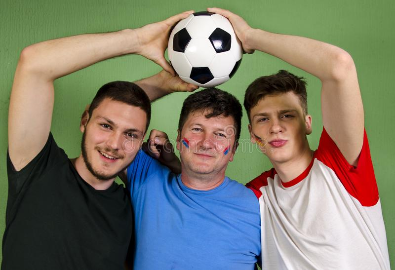 Father and his sons holding soccer ball together stock images
