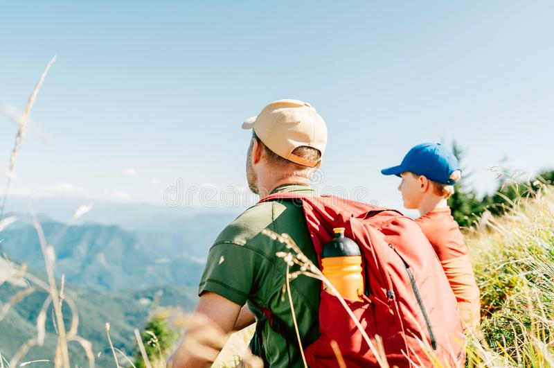 Father and his teenage son sitting on the grass and enjoying mountain landscape during their weekend hiking walking stock photo