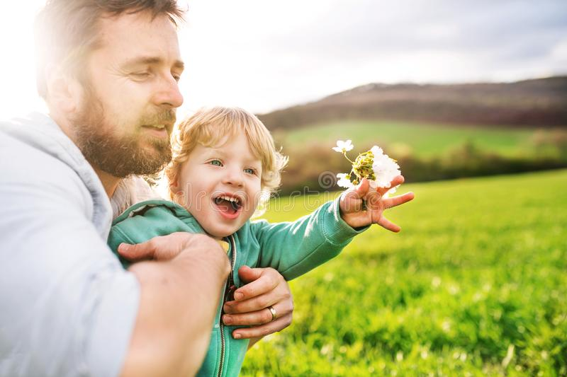A father with his toddler son outside in spring nature. stock photos