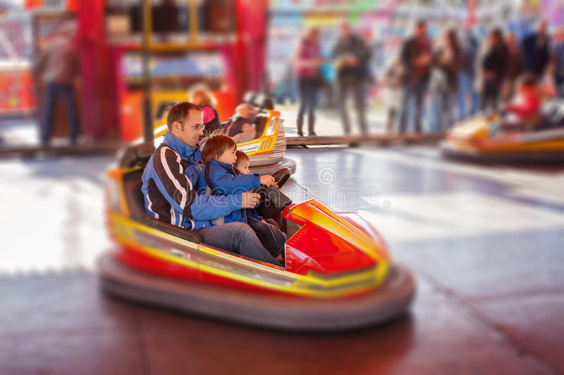 Father and his two sons,l having a ride in the bumper car at the royalty free stock images