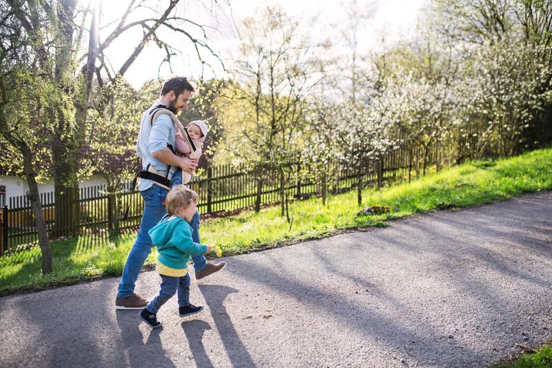 A father with his toddler children outside on a spring walk. stock photography