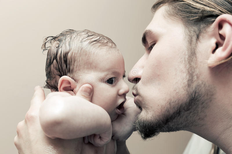 Father with his young baby cuddling and kissing him on cheek stock photos