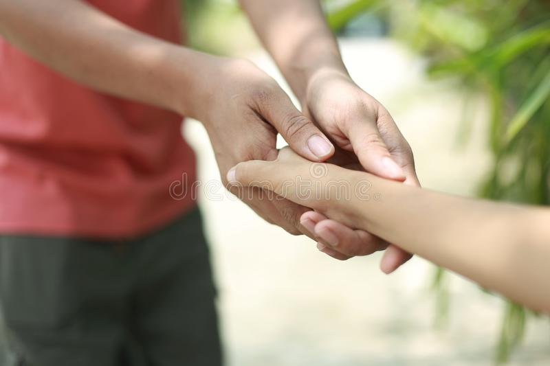 Father hold child hand with love. Family support - Asean father hold child hand with love stock image