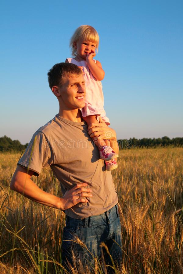 Father hold daughter on shoulder on wheaten field stock photos