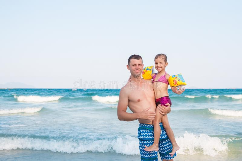 Father holding a baby high with happy face near the sea. Father holding a baby high with happy face near the sea royalty free stock photo