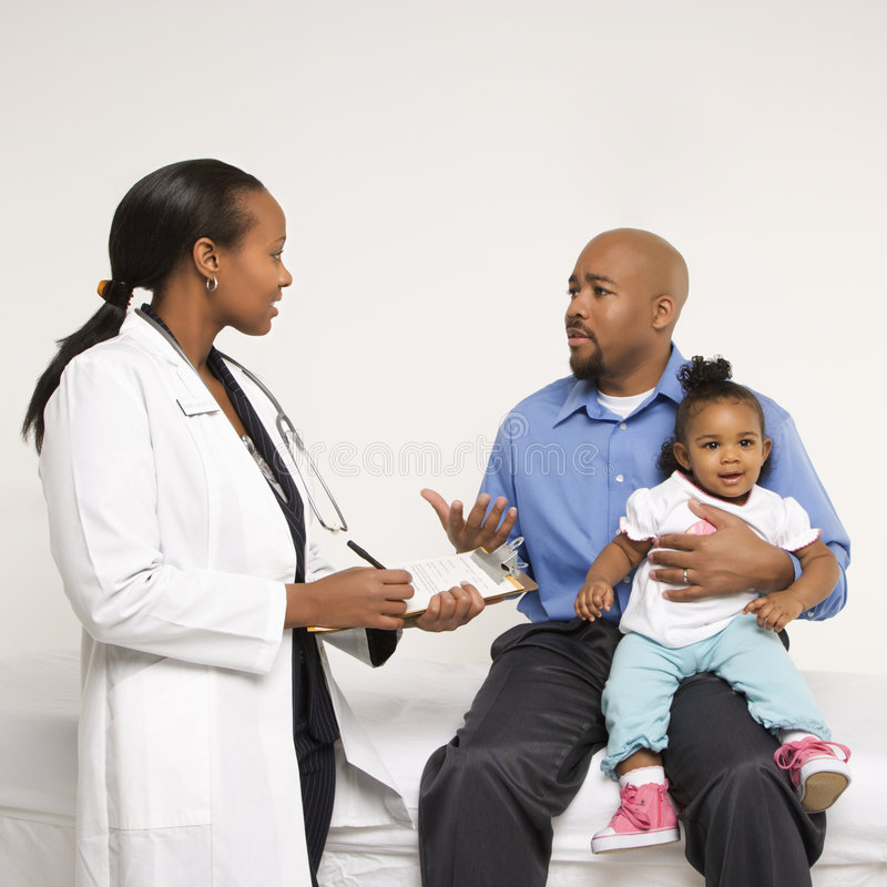 Father holding baby talking to pediatrician. African-American father holding baby girl talking to female pediatrician