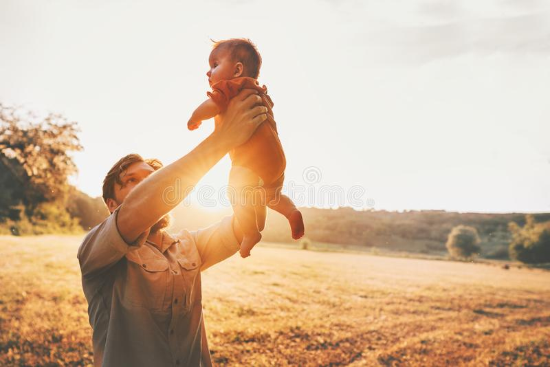 Father holding baby up in the air playing together stock photos