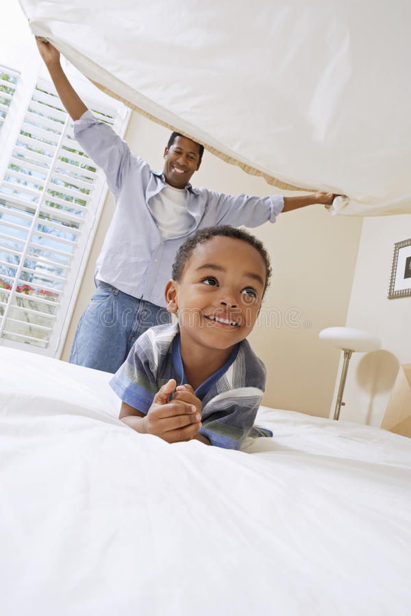 Father Holding Bed Sheet Over Son. Cheerful father holding bedsheet over his little son on bed royalty free stock image