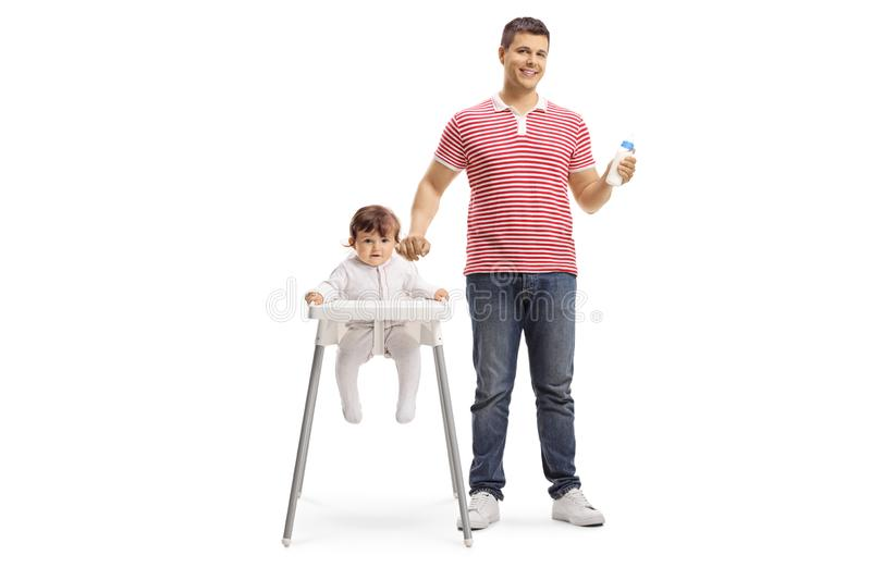 Father holding a boittle and standing next to a baby girl sitting in a feeding chair stock photo