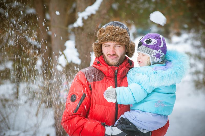 Father holding child in his hands in the winter outdoors and play snowballs royalty free stock photography