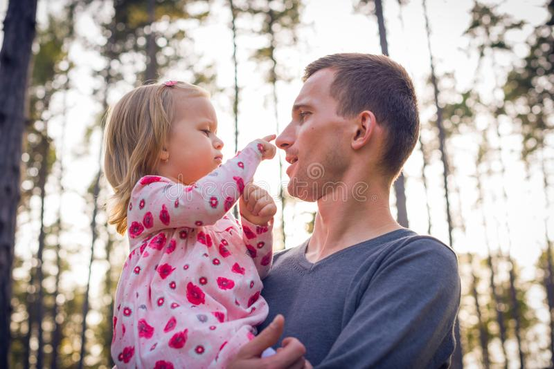 Father holding cute toddler girl daughter in his arms and looking at her. Young father holding cute toddler girl daughter in his arms and looking at her royalty free stock photo