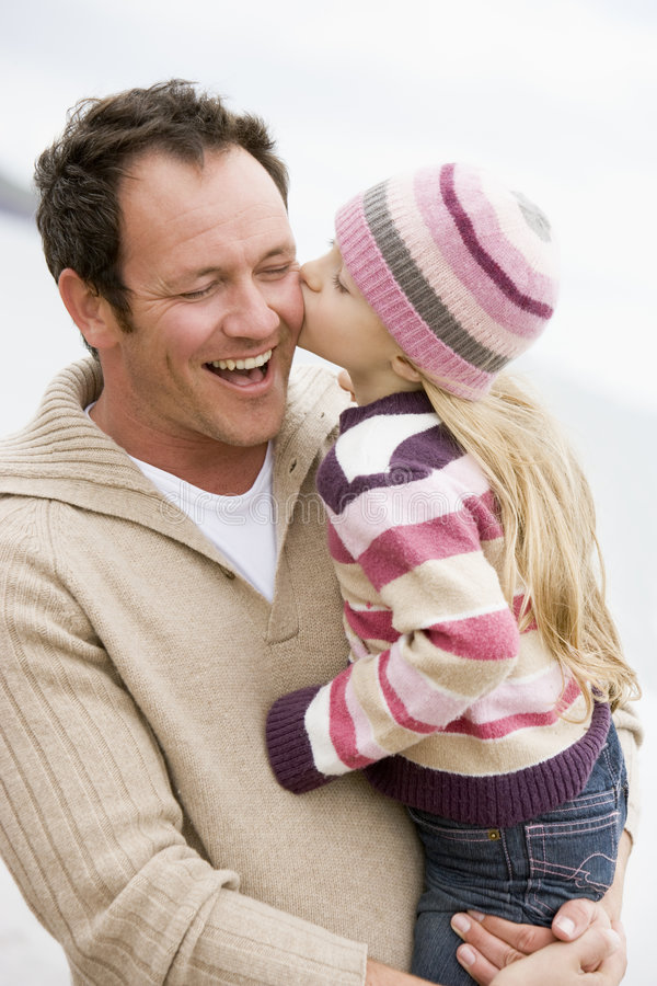Father holding daughter kissing him at beach stock image