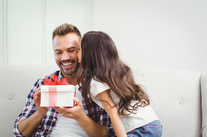 Father holding gift box while daughter kissing. Happy father holding gift box while daughter kissing him stock photos