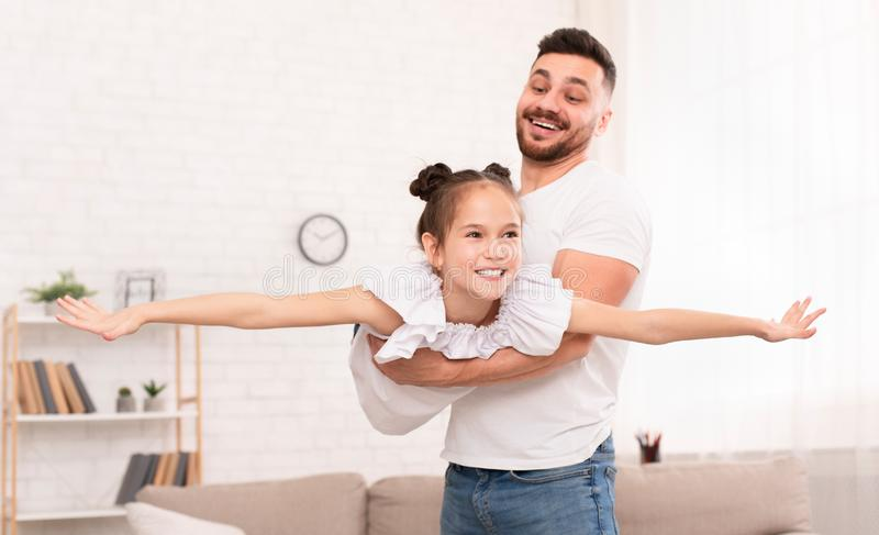 Father holding his cute daughter lying like plane stock photos